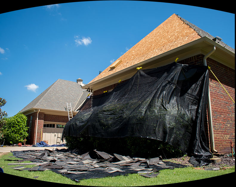 Tarp covering side of house during residential shingle roof replacement project.